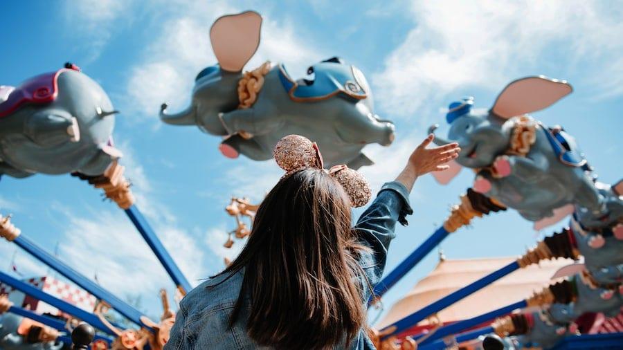 Girl Waving at Flying Dumbo [Source: Disney World]