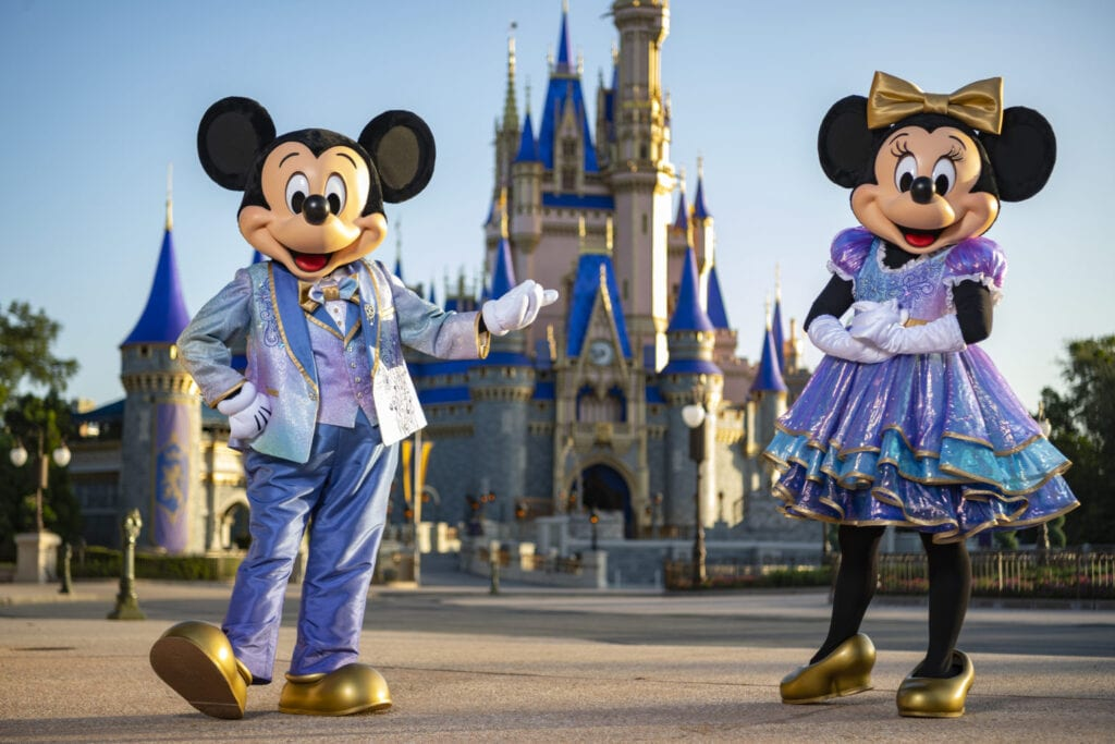 """Beginning Oct. 1, 2021, Mickey Mouse and Minnie Mouse will host """"The World's Most Magical Celebration"""" honoring Walt Disney World Resort's 50th anniversary in Lake Buena Vista, Fla. They will dress in sparkling new looks custom made for the 18-month event, highlighted by embroidered impressions of Cinderella Castle on multi-toned, EARidescent fabric punctuated with pops of gold. (Matt Stroshane, photographer)"""