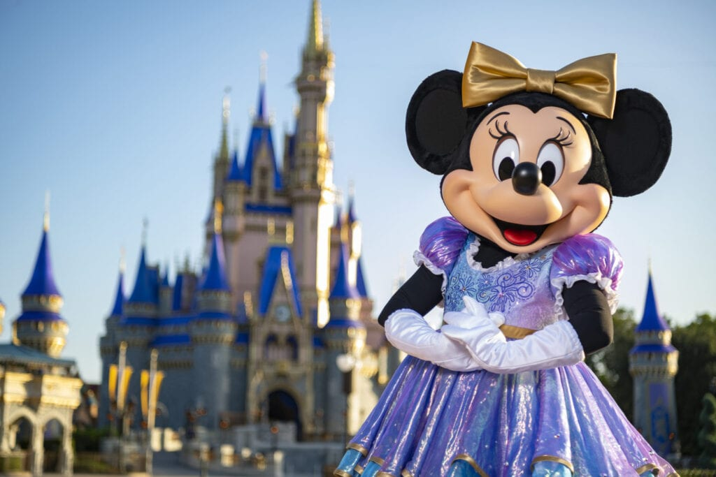 """Beginning Oct. 1, 2021, Minnie Mouse will join Mickey Mouse as hosts of """"The World's Most Magical Celebration"""" honoring Walt Disney World Resort's 50th anniversary in Lake Buena Vista, Fla. They will dress in sparkling new looks custom made for the 18-month event, highlighted by embroidered impressions of Cinderella Castle on multi-toned, EARidescent fabric punctuated with pops of gold. (Matt Stroshane, photographer)"""